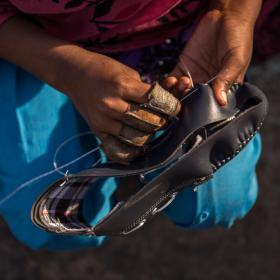 Kanya (12) stitches shoes at her home in Agra, India