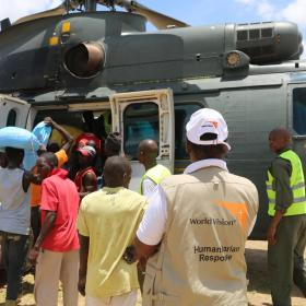 World Vision employees and locals getting food from a helicopter