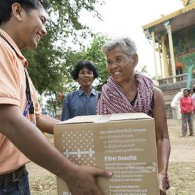 World Vision staff hands community member water filter during flooding event