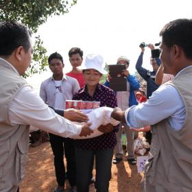 World Vision Cambodia staff members distributing emergency resources to community member in flood affected Cambodia.