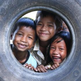 Three Khmer boys poke their heads through an old tire smiling at the camera