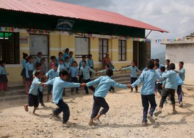 Children play outside a school in Nepal