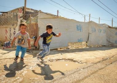 Two boys jumping in puddles at refugee camp