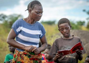 Featured Image: Community reading club volunteer, Jenara Mumbulu, listens to and helps Lightwell, 10, with his reading at a World Vision's reading camp in Zambia. (Photo credit: Laura Reinhardt / World Vision).