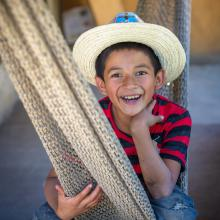 Boy in hat sitting in hammock