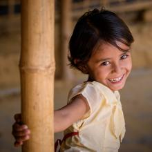 A girl in Bangladesh smiles in her home