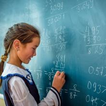 A girl in Mongolia writes on a chalkboard at school