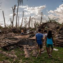 A family in the Philippines surveys the devastation of Typhoon Haiyan