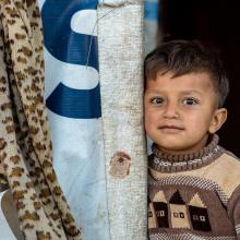 A Syrian boy stands outside his refugee home